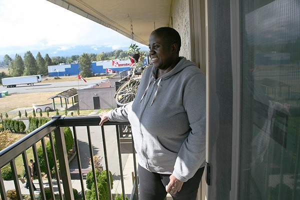 Faith Liddie looks out from her second-floor balcony at The Washington Inn apartments.